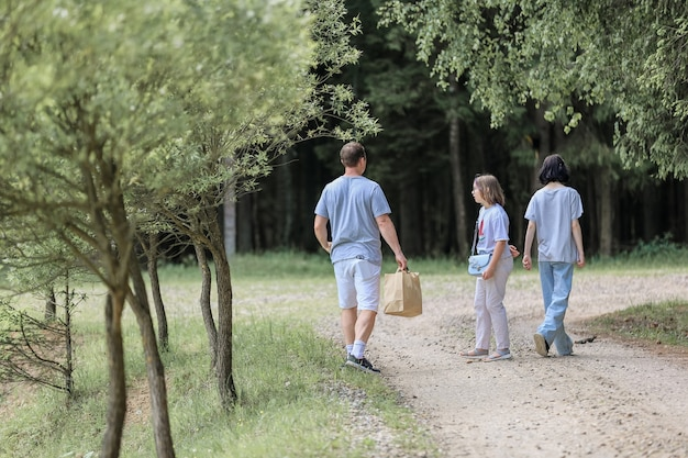 Dad and daughters on a walk in the summer forest