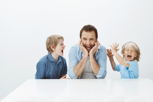 Папе надоело плохое поведение сыновей. портрет недовольного подавленного отца, сидящего за столом и кричащего от депрессии, в то время как дети кричат и дурачатся