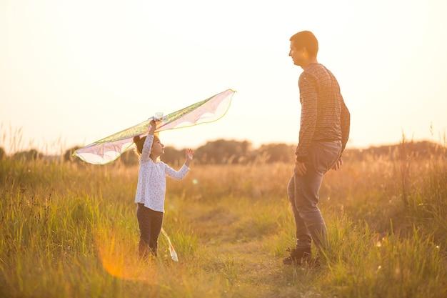 お父さんは、娘が夏の日没時に畑で凧を飛ばすのを手伝っています。屋外での家族向けエンターテインメント、父の日、こどもの日。農村地域、サポート、相互支援。太陽のオレンジ色の光