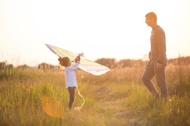아빠는 해가 질 때 여름에 들판에서 딸이 연을 날 수 있도록 도와줍니다. 가족 엔터테인먼트 야외, 아버지의 날, 어린이 날. 농촌 지역, 지원, 상호 지원. 태양의 오렌지 빛