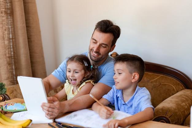 아빠는 두 자녀(여자아이와 남자아이)가 집에서 원격 학습을 공부하는 동안 태블릿에서 온라인 수업을 시작하도록 돕습니다.