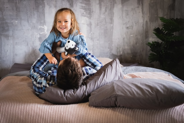 Dad and his daughter play on the bed in the bedroom, smiling and laughing