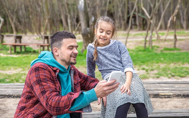 Dad and his little daughter look at the phone while walking in the woods.