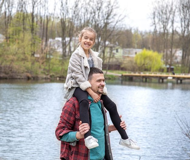 Dad and his little daughter in the woods for a walk by the river.