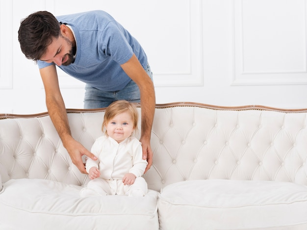 Dad holding baby on sofa