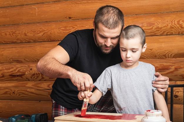 아빠는 손에 빨간 페인트가있는 붓을 들고 나무 표면을 칠하고 아들에게 그림을 그리도록 가르칩니다.