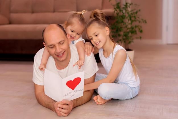お父さんが家の休日の父の日に小さな娘からのカードを保持しています。