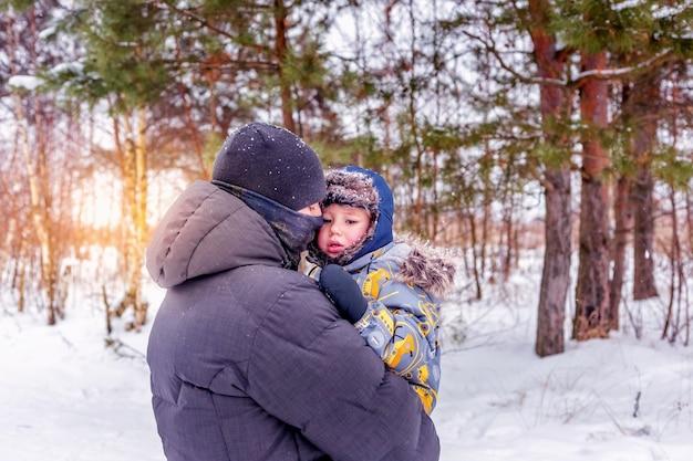 아빠는 눈 덮인 숲이나 겨울 공원에서 어린 아들을 안고 안아줍니다. 가족을 위한 겨울 야외 활동의 개념입니다.