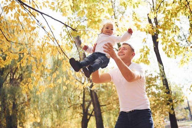 아빠는 딸을 손에 들고 가을 공원에서 즐거운 시간을 보낸다.
