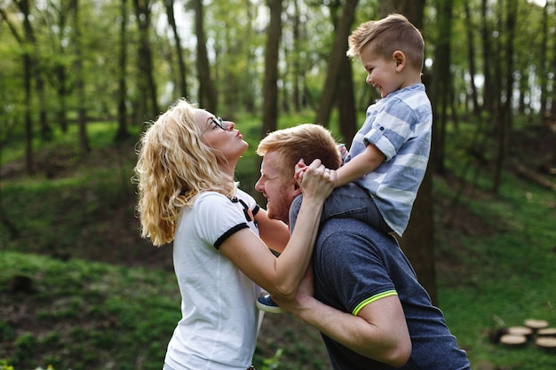 Dad holds his son on the neck and plays with a mom in a green summer park