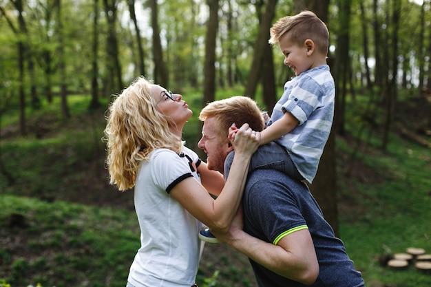 お父さんは首に息子を抱き、緑の夏の公園でお母さんと遊ぶ