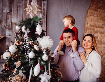 Dad holds little daughter  on his neck posing with mom before a rich Christmas tree
