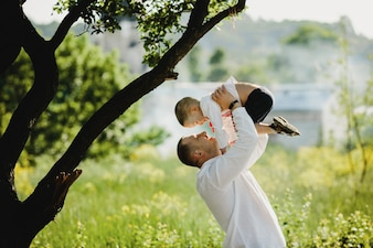Dad holds little son in embroidered shirt in his arms standing under green tree
