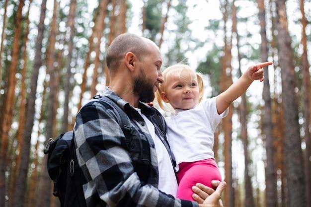 お父さんは森の中をハイキングしている間、赤ちゃんを腕に抱きます。山や森への家族のハイキング。