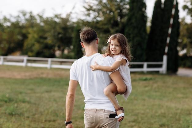 Папа обнимает дочь любит гулять на свежем воздухе и смотреть на природу. молодая семья проводит время вместе в отпуске, на открытом воздухе.