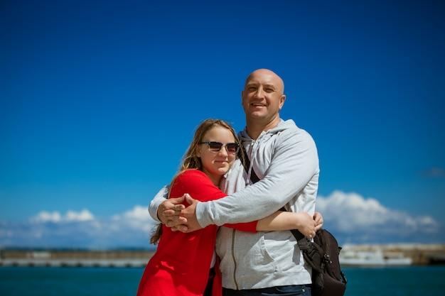 Папа обнимает свою дочь на фоне моря, концепция семейного путешествия