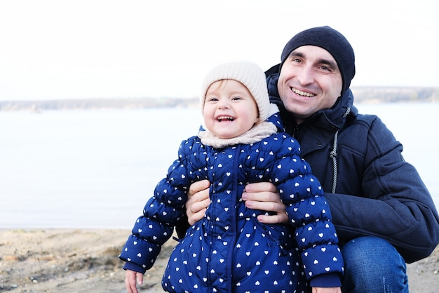 Папа обнимает свою маленькую дочку, и они смеются - папа с маленькой девочкой смеются на пляже