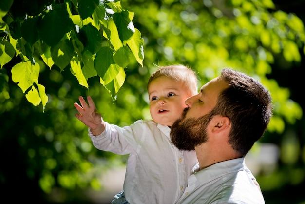 Папа обнимает своего маленького сына в парке