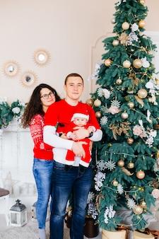 아빠는 뒷면에서 아들을 껴안고 엄마는 벽난로 근처의 뒷면에서 아빠를 껴안고 아름답게 장식 된 크리스마스 트리