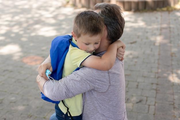 Dad hugs son in front of school or kindergarten doors