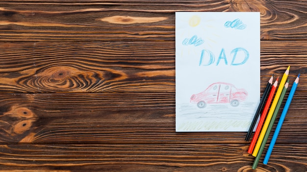 Dad inscription with car drawing on paper sheet
