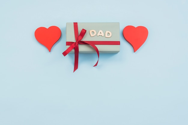 Dad inscription with gift box and hearts on table