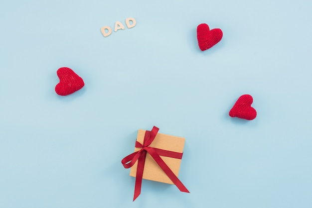 Dad inscription with gift box and red toy hearts