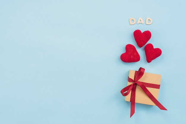 Dad inscription with gift box and toy hearts