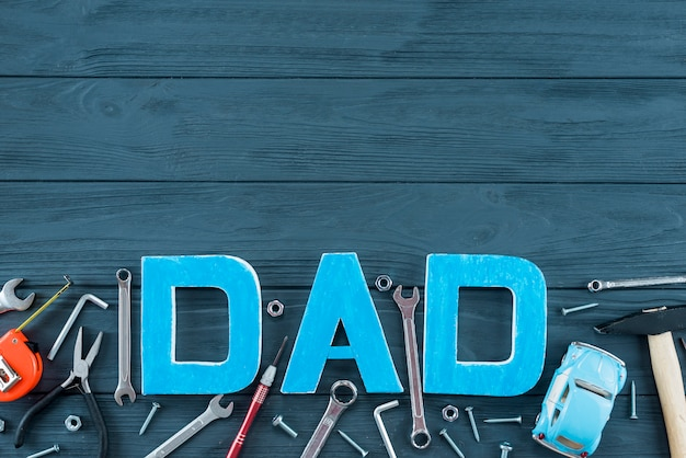 Dad inscription with tools and toy car on table Free Photo