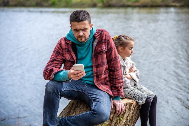 아빠는 딸에게 신경을 쓰지 않고 전화를 확인하고 숲을 산책하고 있습니다.