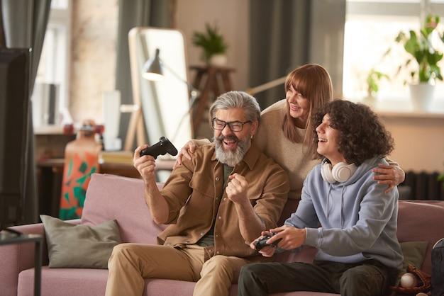お父さんは、家で一緒にビデオゲームをしているときに息子を勝ち取ったゲームでの勝利に満足しています。