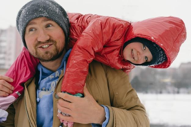 Папа держит на плечах маленькую дочку.