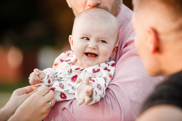 Dad is holding little cute smiling daughter in arms. family spending summer time together, outside, on vacation, outdoors on sunset. the concept of family holiday.