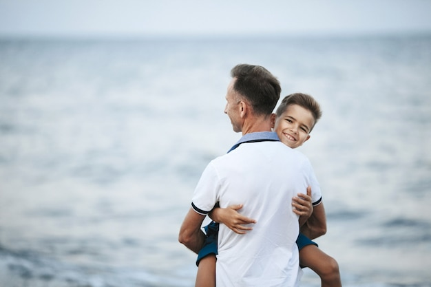 Dad is holding son on the hands and child is looking straight and smiles on the seashore