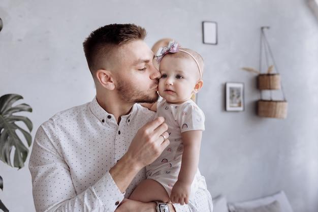 お父さんは子供の娘にキスをして抱きしめています。幸せな家族と父の日。
