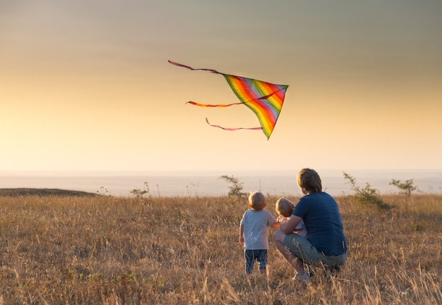 Dad and kids boys fly a kite at sunset