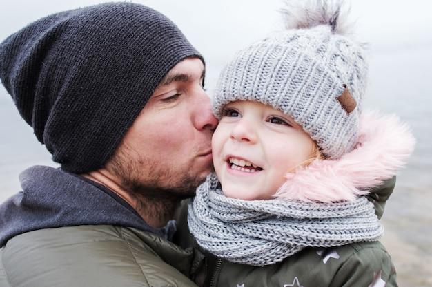 Папа целует свою маленькую дочку, и они радуются своим отношениям - отец и дочь веселятся вместе