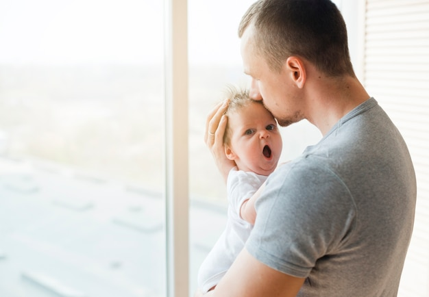Папа целует ребенка с открытым ртом во лбу