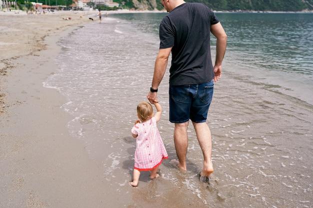 お父さんは砂浜に沿って手で小さな女の子を導きます