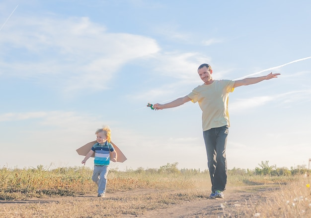 Dad and little son run along the road on the road and pretend to be an airplane. father and son games