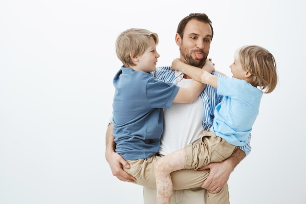Dad loves spending time with family. carefree happy father holding sons in arms and sticking out tongue