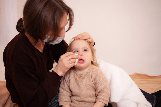 Dad in a mask wipes his daughter's nose. the child's snot, empty space for text. colds, flu, home quarantine, sick child.