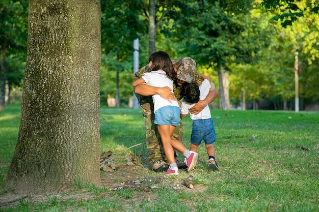Papà che incontra due bambini dopo il viaggio di missione militare, abbracciando i bambini sull'erba nel parco.
