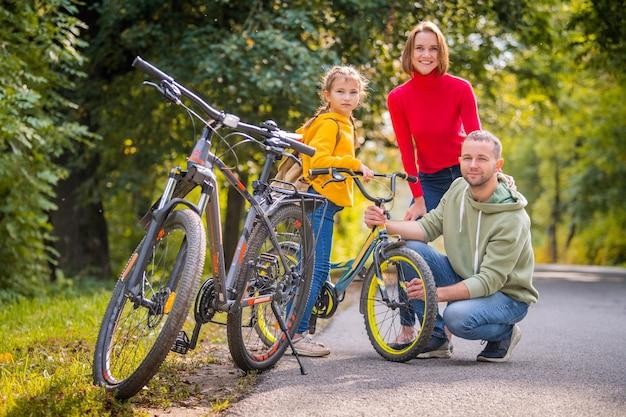 Папа, мама и дочка гуляют на велосипедах по осенней дорожке парка.