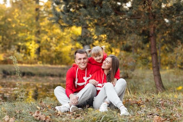 お父さん、お母さん、秋の公園で遊んでいるかわいい娘。