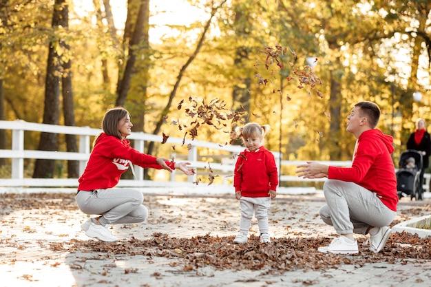 秋の公園でお父さん、お母さん、小さなかわいい娘が葉で遊んで遊んでいます。