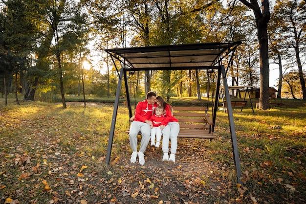 Папа, мама и дочка сидят на деревянных качелях в осеннем парке