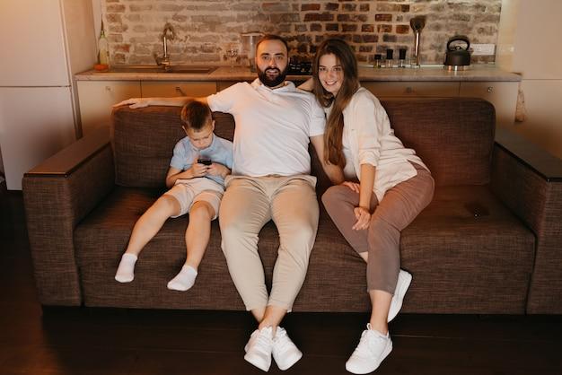 아빠, 엄마, 아들은 저녁에 소파에서 tv를보고 있습니다. 집에서 친척. 아들은 가족 근처에서 휴대폰으로 게임을하고 있습니다.