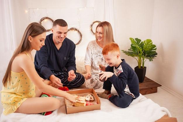 Папа, мама, дочь и сын едят вкусные торты и сладости в своей спальне