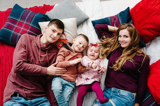 Папа, мама обнимает маленького сына и дочь на кровати в спальне